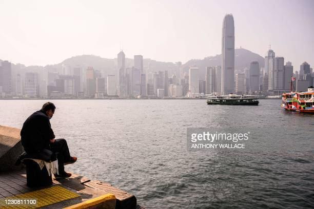 Man sits on a bollard in the Kowloon side of Victoria Harbour, with a view of the Hong Kong Island skyline in the background on January 27, 2021.