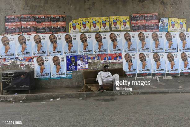 A man sits on a broken sofa in front of a wall displaying election campaign posters in Lagos Nigeria Saturday Feb 16 2019 A lastminute delay of...