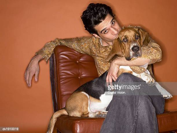 Man Sits on a Brown Leather Chair Kissing a Basset Hound on Its Head