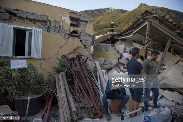 A man sits on a bucket as others look on near a wracked building after 40magnitude richter scale earthquake hit Ischia Island's Casamicciola Terme of...