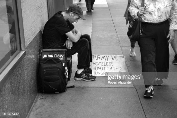 A man sits on a busy New York City sidewalk with a sign declaring he is a homeless military veteran