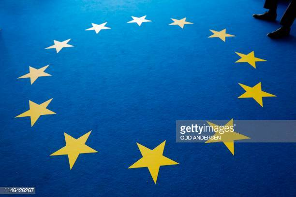 Man sits on a carpet in the design of the European flag during a press conference of Germany's conservative CDU party following a meeting of the...
