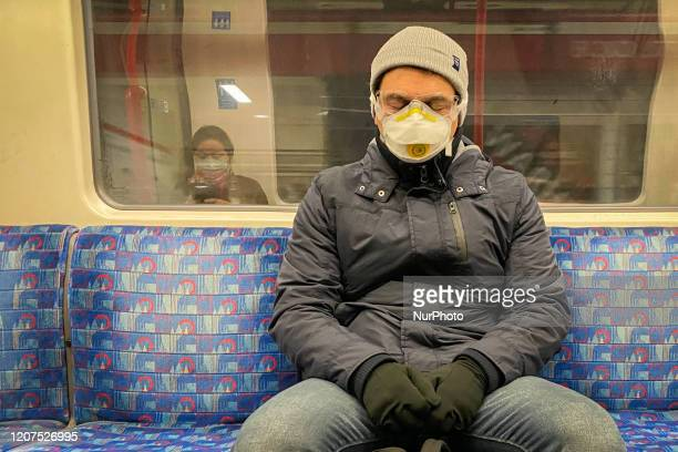 A man sits on a Central Line train as he wears a protective mask and glasses and a woman wearing mask is reflected on the train window during the...