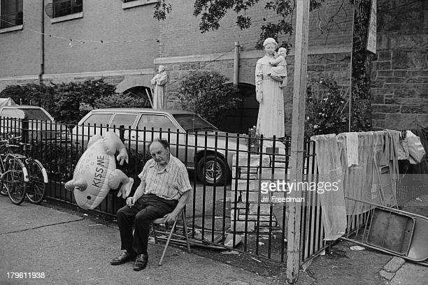 A man sits on a chair outside the front of St Anthony of Padua Church Sullivan Street Greenwich Village New York City 1979