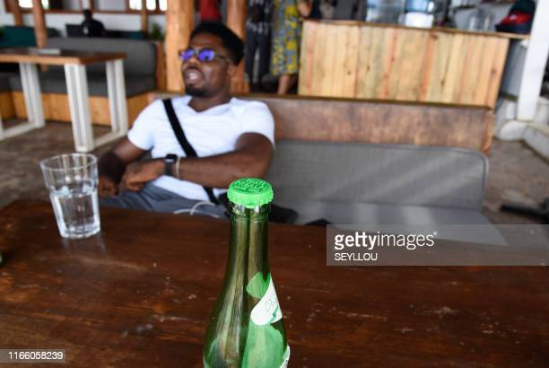 A man sits on a couch by a bottle with a collected capsule laying on a table at the Copacabana restaurant on Yoff Virage beach in Dakar on September...