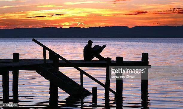 A man sits on a dock reading a newspaper at the beach of Ammersee Lake the mild winter evening on January 10 2007 in Herrsching Germany Bavaria and...