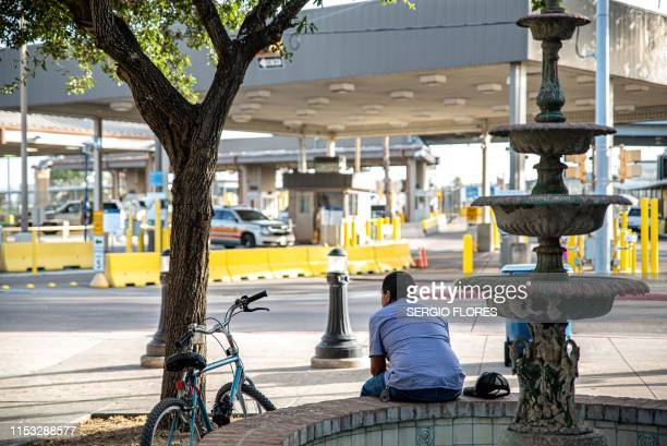 Man sits on a fountain just across the street from the border crossing in Brownsville, Texas on June 29, 2019. - Border cities like Matamoros,...
