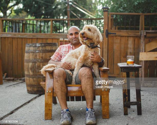 a man sits on a handmade wooden chair with a happy dog on his lap - bourbon whiskey stock-fotos und bilder