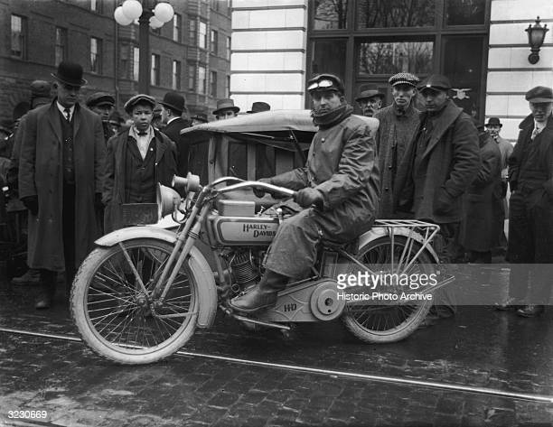 A man sits on a HarleyDavidson motorcycle as a group of men stand around him on SW Broadway and Yamhill Streets in downtown Portland Oregon He wears...
