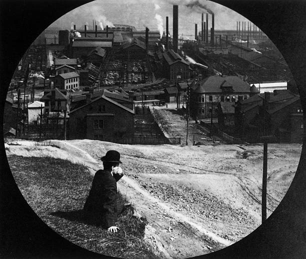 A man sits on a hill overlooking the Homestead steel...