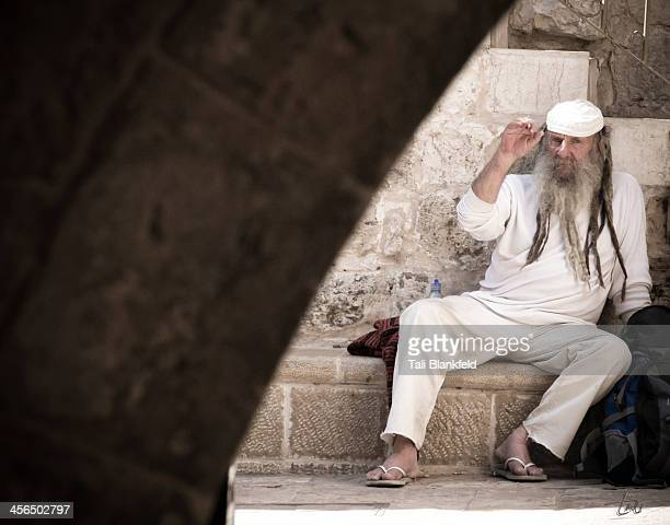 Man sits on a ledge in the Greek Orthodox section of the Old City in Jerusalem, Israel.