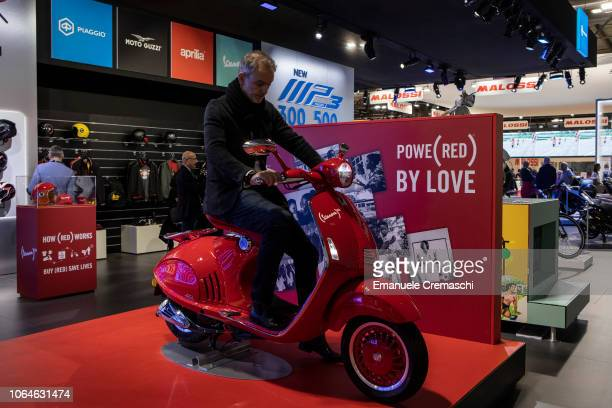 Man sits on a limited edition of the iconic Vespa scooter during the 76th edition of EICMA on November 7, 2018 in Milan, Italy. EICMA is an...