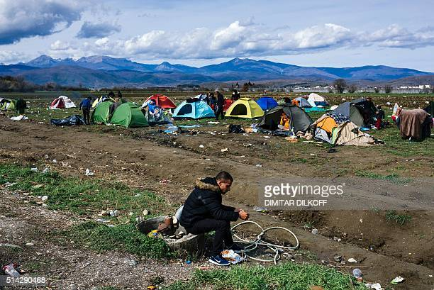 A man sits on a low wall as people go about with their daily life at a makeshift camp at the GreekMacedonian border near the Greek village of Idomeni...
