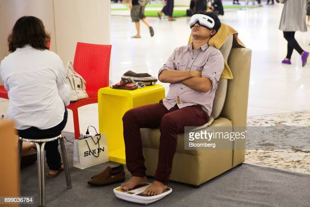 A man sits on a massage chair inside the Junction City mall in Yangon Myanmar on Friday June 16 2017 A pariah state for decades Myanmars recent...