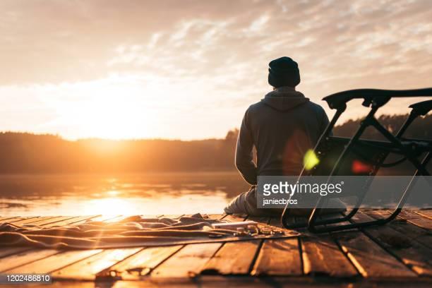 el hombre se sienta en un muelle en el lago - un solo hombre fotografías e imágenes de stock