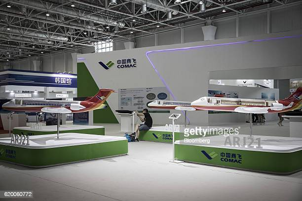 A man sits on a podium as various Commercial Aircraft Corp of China ARJ21 models stand on display at the China International Aviation Aerospace...