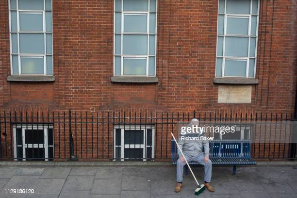A man sits on a public bench with a new longhandled brush on the Walworth Road on 5th March 2019 in London England
