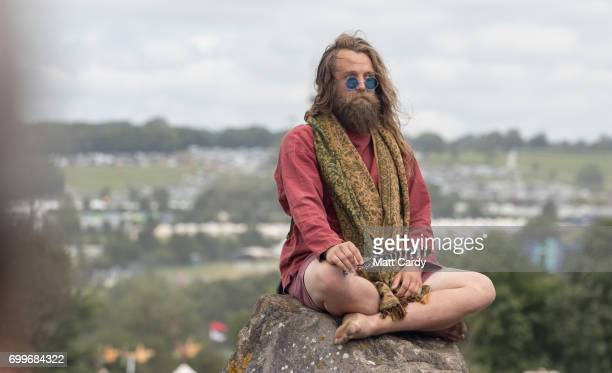 GLASTONBURY ENGLAND JUNE A man sits on a rock at the Stone Circle at the Glastonbury Festival at Worthy Farm in Pilton on June 22 2017 near...