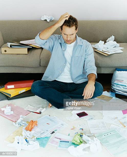 Man Sits on a Rug Surrounded by Bills and Folders, Scratching his Head