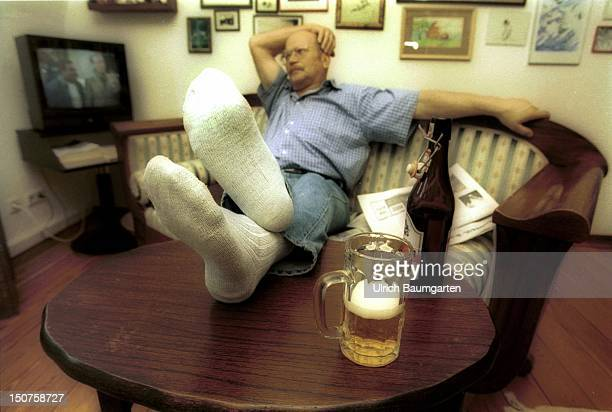 A man sits on a sofa with his feets on the table beside beer glass and beer bottle in the background the television moves