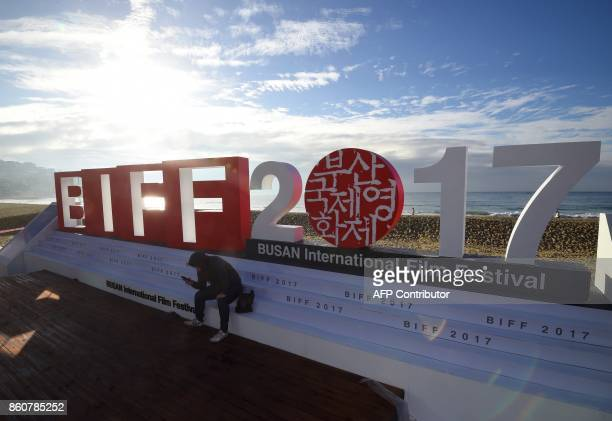 A man sits on a stage of the BIFF Village a venue of the 22nd Busan International Film Festival at Haeundae beach in Busan on October 13 2017 BIFF...