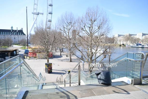 A man sits on a step leading down to the South Bank of the River Thames in central London in the morning on March 24 2020 after Britain ordered a...