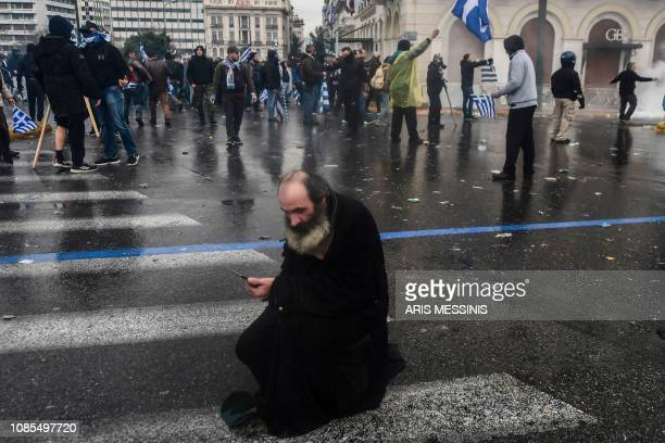 A man sits on a street during a demonstration against the agreement with Skopje to rename neighbouring country Macedonia as the Republic of North...