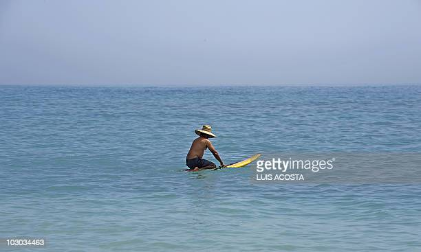 A man sits on a surfboard at Cabo Pulmo National Marine park in Baja California State Mexico on June 22 2010 Cabo Pulmo National Park is one of the...