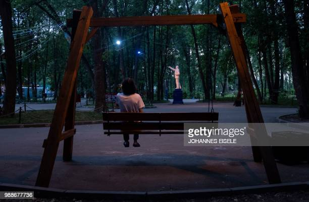 A man sits on a swing facing a statue of Vladimir Lenin the founder of the Soviet Union in a park in Nizhny Novgorod on July 1 2018