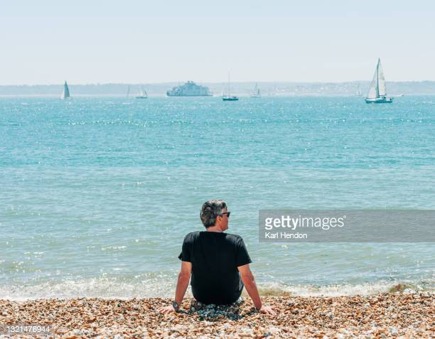a man sits on an english beach on a sunny day - stock photo - passenger craft stock pictures, royalty-free photos & images