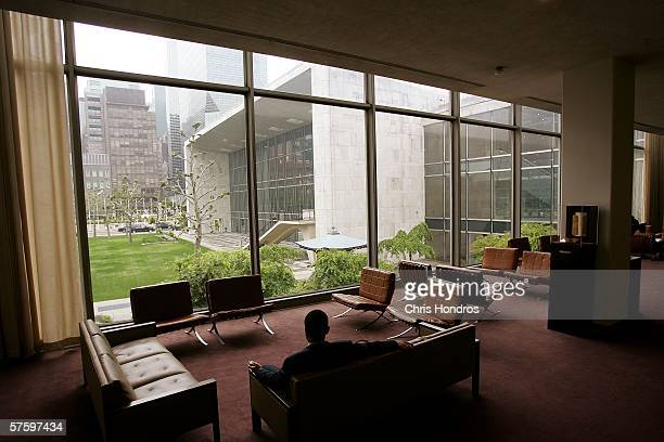 A man sits on couches looking out onto the north end of the General Assembly building of the United Nations May 12 2006 at the United Nations...