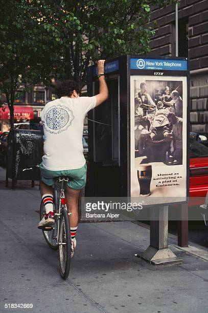 Man sits on his bicycle using a telephone booth, New York City, USA, May 1993.