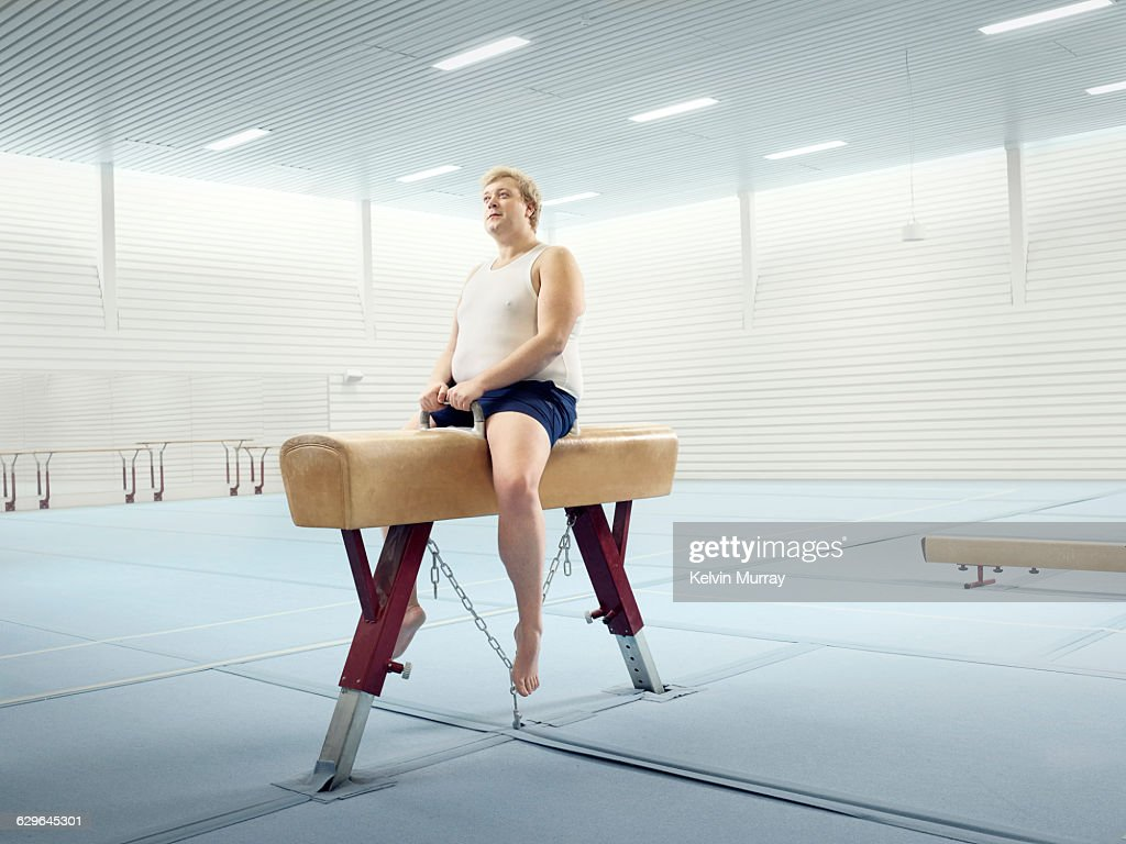 Man sits on horse in gymnasium : Stock Photo