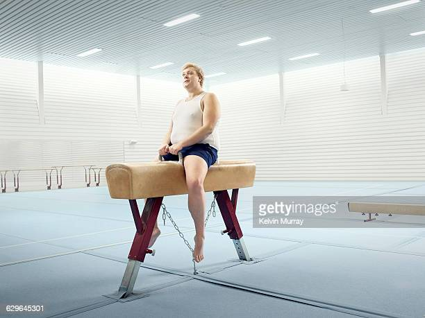 Man sits on horse in gymnasium