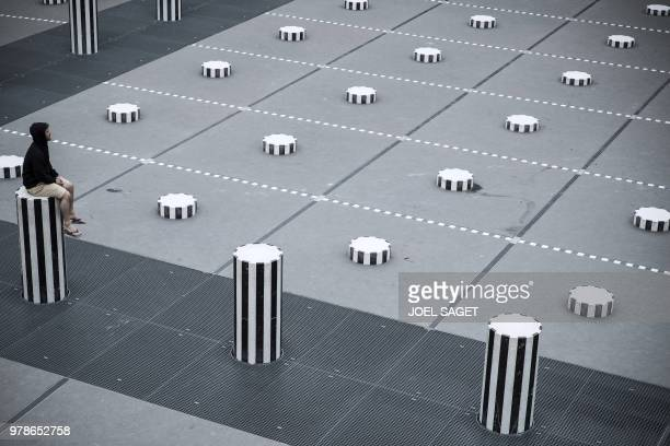 A man sits on one of the Colonnes de Buren an art installation by French artist Daniel Buren in the inner yard of the Palais Royal gardens on June 19...