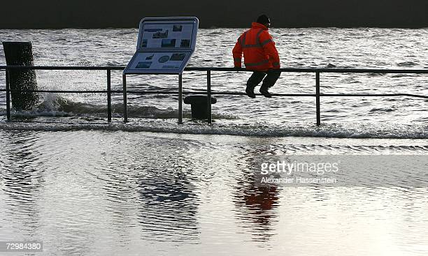 A man sits on railings and watches as the River Elbe begins to flood the edge of the harbour in the Fischmarkt area of Hamburg on January 12 2007...