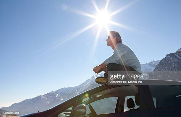 Man sits on roof of car with sun overhead, mtns