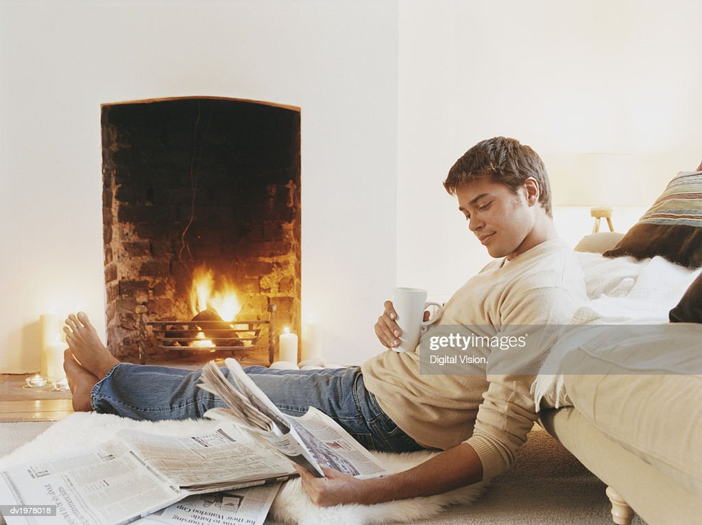 Man Sits on Rug by Fireplace Holding a Cup and Reading a Newspaper : Stock Photo