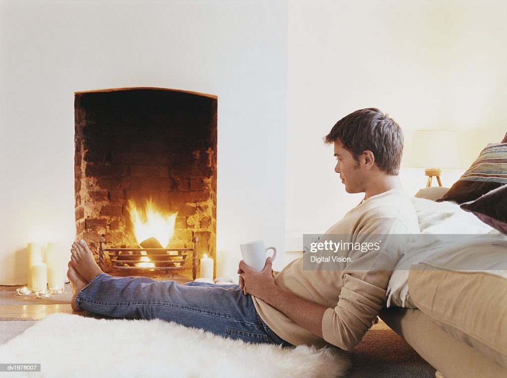 Man Sits on Rug Holding a Cup and Looking at Fireplace : Stock Photo