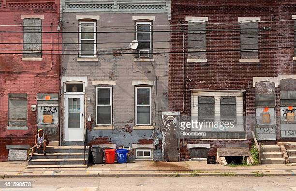Man sits on stairs on the street in front of an abandoned home in Camden, New Jersey, U.S., on Monday, June 23, 2014. Artist Chris Toepfer, founder...