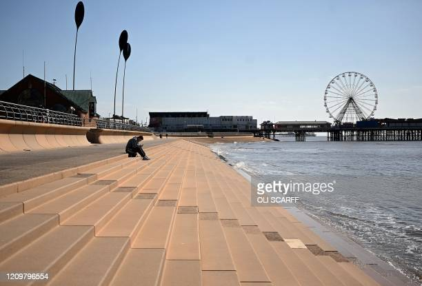 Man sits on steps leading down to the sea, near the central pier in the spring sunshine on the coast in Blackpool, north-west England on April 13...
