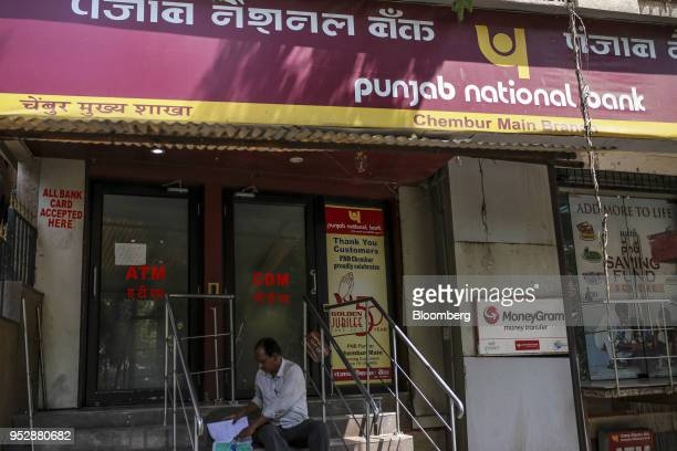 A man sits on steps outside a Punjab National Bank branch in Mumbai India on Saturday April 21 2018 PNB is scheduled to announce full year earnings...