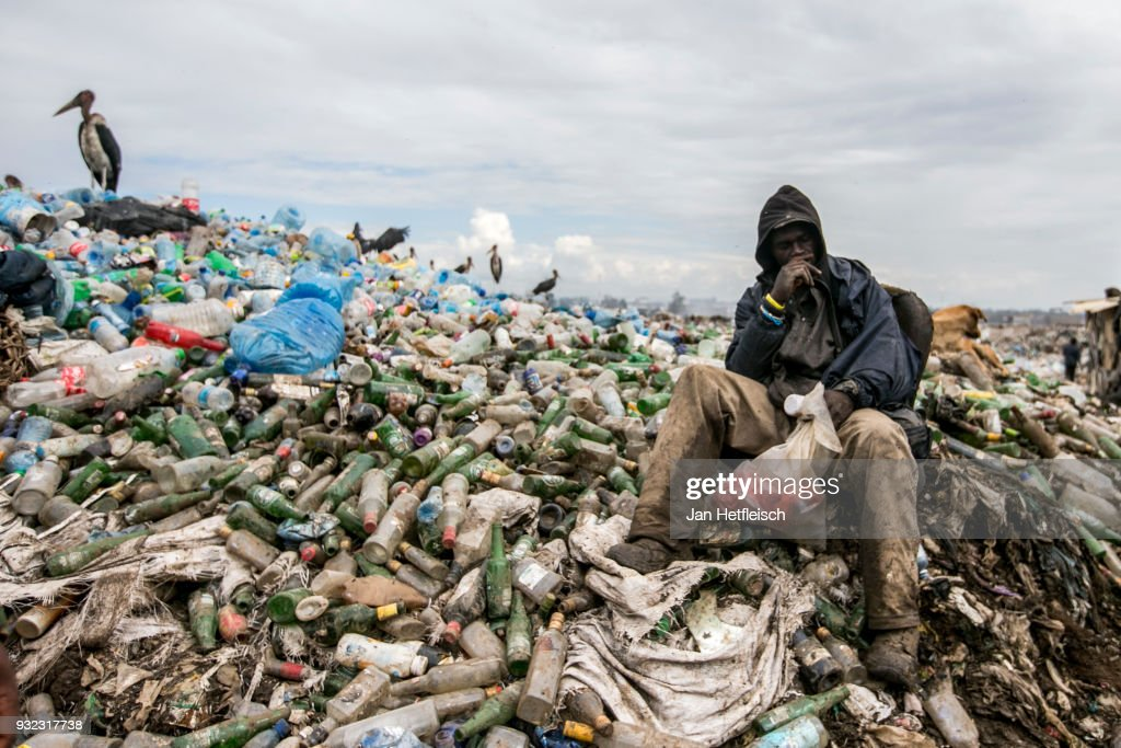 A man sits on the Dandora rubbish Dump on March 14, 2018 in Nairobi, Kenya. The Dandora landfield is located 8 Kilometer east of the city center of Nairobi, the capital of Kenya. Every day, more than 2.000 metric tonnes of waste are dumped on this site. More than 3000 pickers work day by day at the sprawling 30-acre rubbish dump.