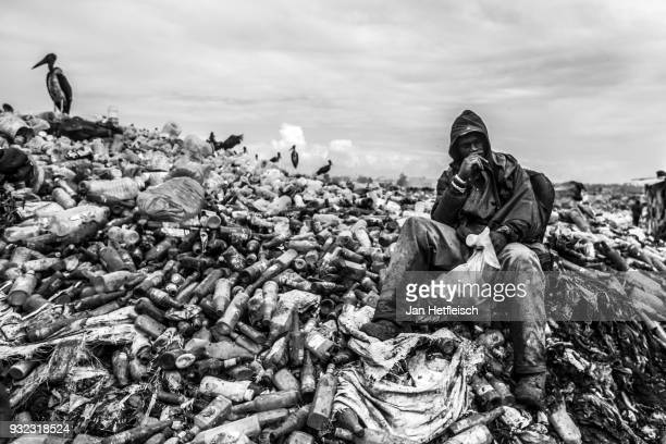 A man sits on the Dandora rubbish Dump on March 14 2018 in Nairobi Kenya The Dandora landfield is located 8 Kilometer east of the city center of...
