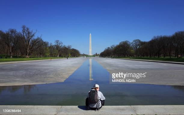 A man sits on the edge of the Reflecting Pool which has been drained for maintenance on the Mall in Washington DC on March 26 2020 After days of...