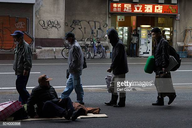 A man sits on the ground as homeless people queue to access a shelter in the slum area of Kamagasaki on April 23 2016 in Osaka Japan Kamagasaki a...