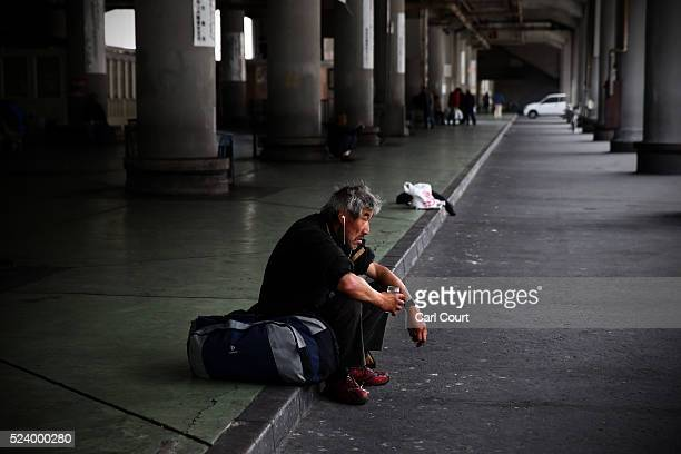 A man sits on the ground in the slum area of Kamagasaki on April 23 2016 in Osaka Japan Kamagasaki a district in Japan's second largest city Osaka is...