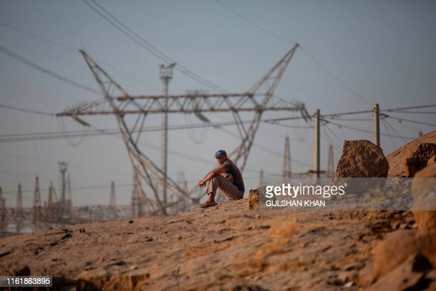 """Man sits on the """"koppie"""" close to the Lonmin owned mine, now controlled by Sibanye Stillwater, in Marikana, Rustenberg where striking miners were..."""