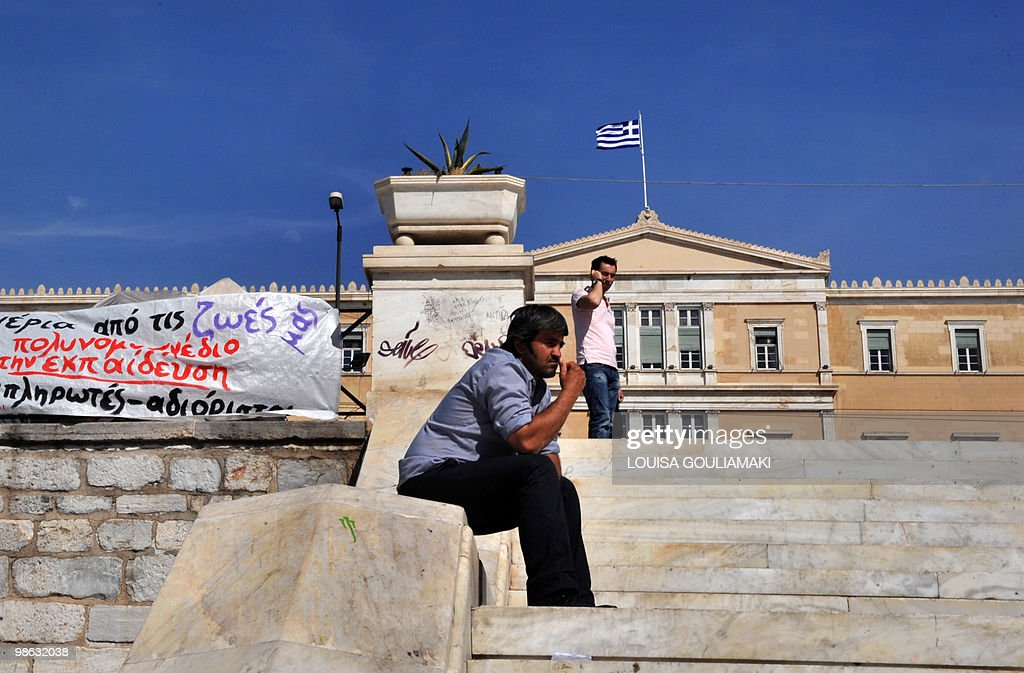 A man sits on the stairs next to banners staged by unemployed teachers during their protest outside the Greek parliament in Athens on April 23, 2010. Greece appealed for a debt rescue from the EU and IMF on Friday and said that help should arrive within days, in a dramatic turn for the eurozone at risk from Greek contagion. Prime Minister George Papandreou told his nation in a televised speech that the aid was a 'national need' which would 'offer us a safe port to allow our boat to float again.'