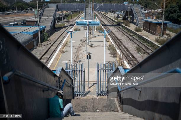 Man sits on the stairs of the dilapidated Wonderboom train station is seen in Pretoria, on March 10, 2021. - South Africa's metro rail infrastructure...
